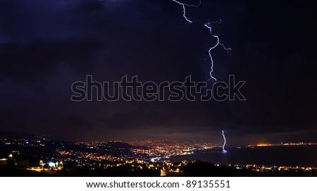 Lightning, thunderstorm at night sky, overcast winter weather with dramatic sky over city - stock photo
