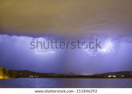 Lightning with rain coming down over the front range of the Colorado Rocky Mountain foothills. - stock photo
