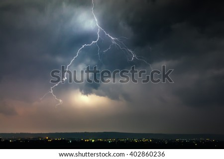 Lightnings over city during thunderstorm in the night - stock photo