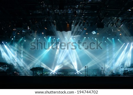 Lights beams on stage with piano and musical instruments - stock photo
