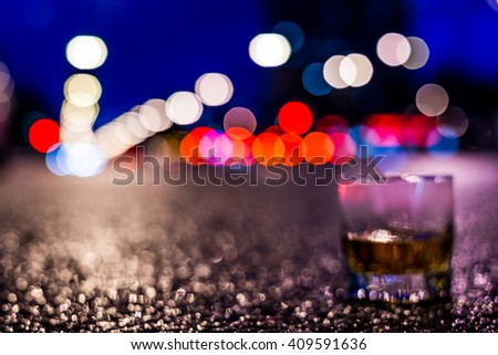 Lights of the city at night through the glass of alcohol, headlights of the approaching cars. View from the glass level with brandy standing on the asphalt, defocused image, in blue tones - stock photo