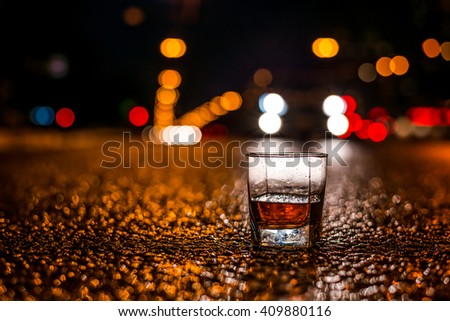 Lights of the city at night through the glass of alcohol, near the car rides. View from the glass level with brandy standing on the asphalt - stock photo