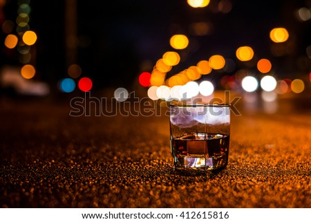 Lights of the city at night through the glass of alcohol, night avenue in the light of a passing car headlights. View from the glass level with brandy standing on the sidewalk - stock photo