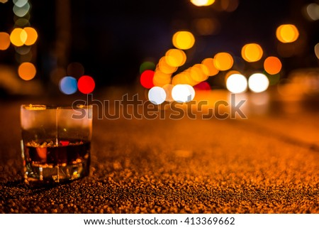 Lights of the city at night through the glass of alcohol, night avenue in the light of a passing car headlights. View from the glass level with brandy standing on the sidewalk, focus on the asphalt - stock photo