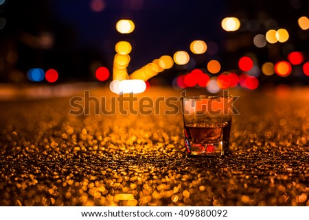 Lights of the city at night through the glass of alcohol, night ?venue in the light of car headlights. View from the glass level with brandy standing on the asphalt - stock photo