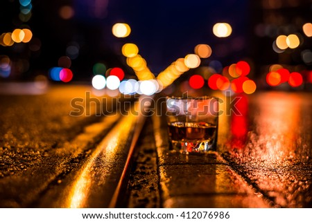 Lights of the city at night through the glass of alcohol, night ?venue with rails for trams. View from the level of the rails on which stands a glass of brandy, focus on the asphalt - stock photo