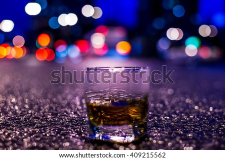 Lights of the city at night through the glass of alcohol, parking lights of the cars. View from the glass level with brandy standing on the asphalt, in blue tones - stock photo