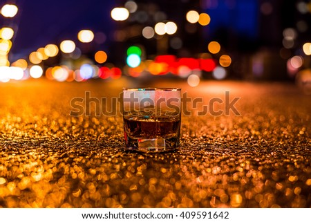Lights of the city at night through the glass of alcohol, parking lights of the cars. View from the glass level with brandy standing on the asphalt - stock photo