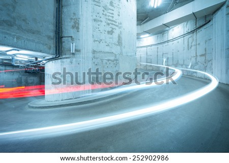 Lights of the moving car above the spiral road to the underground parking. - stock photo
