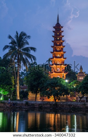 Lights of Tran Quoc Pagoda reflected in lake by night, Hanoi - stock photo