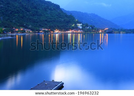 Lights reflect on a lake from shoreline houses that sit beneath a large forested hill. - stock photo