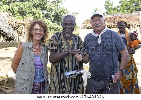 LIGUIDI MANGAM, BURKINA FASO - NOVEMBER 11 : two French tourists makes a visit to a village in Burkina Faso, november 11, 2010 - stock photo