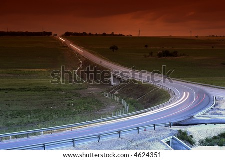 lihgt tracks over the highway by night - stock photo