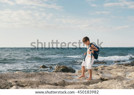 Liittle boy on a rock in sea waves