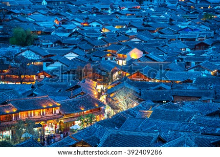 Lijiang Old Town bird eye top top view with local historical architectures roof building in night scene - stock photo