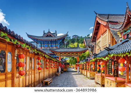 LIJIANG, YUNNAN PROVINCE, CHINA - OCTOBER 23, 2015: Scenic street decorated with traditional Chinese red lanterns in the Old Town of Lijiang. Lijiang is a popular tourist destination of Asia. - stock photo