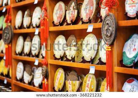 LIJIANG, YUNNAN PROVINCE, CHINA - OCTOBER 23, 2015: Traditional Chinese tea on wooden shelves at tea shop in the Old Town of Lijiang. Disks of Yunnan Puer tea. Shallow depth of field.