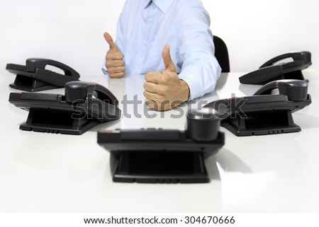 like hand with office phones on desk - stock photo