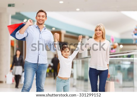 Like my parents. Cheerful vivacious family holding their hands together and having shopping while walking around the mall - stock photo