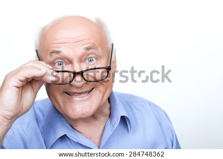 Like reading. Pleasant grandfather wearing glasses and holding them while smiling on white background. - stock photo
