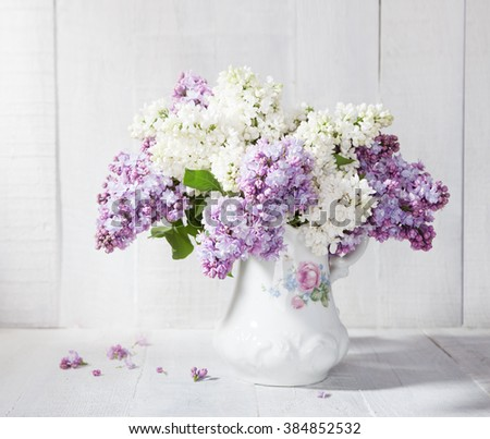 Lilac bouquet in ceramic jug against a white wooden wall.