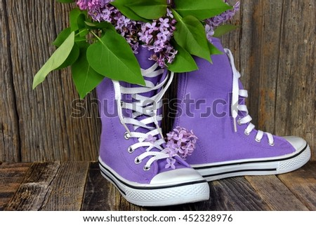 lilac bouquet in pair of high top purple sneakers on rustic barn wood - stock photo