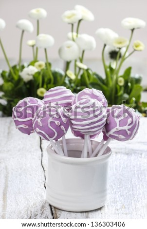 Lilac cake pops in white ceramic jar. White daisies in the background. Party table setting. - stock photo