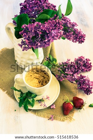 Lilac flowers and cup of coffee with good morning note on rustic wooden background