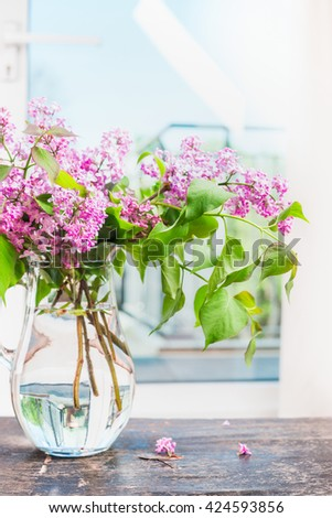 Lilac flowers bunch in glass vase on window still, indoor.