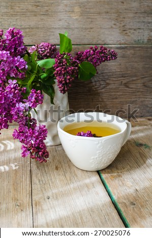 Lilac flowers in a pot and cup of tea in rustic interior - stock photo