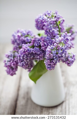 Lilac flowers in white vase - stock photo