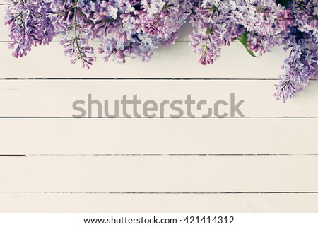 Lilac flowers on vintage wooden background. Top view, copy space - stock photo