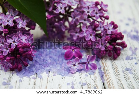 Lilac flowers with sea salt on a old wooden table