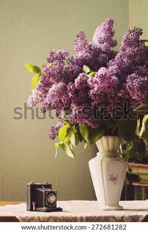 Lilac in a Vase and toy camera - stock photo