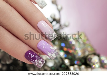 Lilac nail Polish with sparkles and snowflakes on the background of Christmas tree decorations. - stock photo
