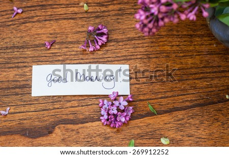 Lilac on the wooden background with good morning note