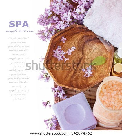 lilac spa (fresh lilac flowers,spa salt, zen stones, Herbal massage balls, towel) on a wooden bord (with easy removable text) - stock photo