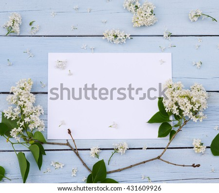 Lilac spring flowers with blank paper for greeting message on a light blue shabby wooden background. Vintage Floral mock up with white flowers. Copy space - stock photo