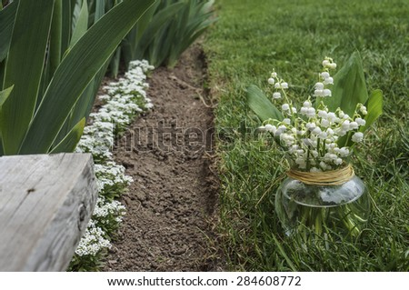 Lilies of the valley in a vase on the grass