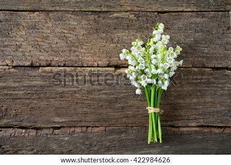 lilies of the valley on the wooden surface