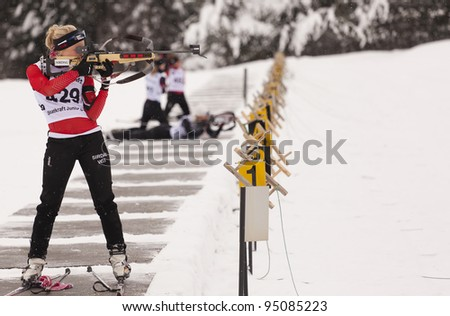 LILLEHAMMER, NORWAY – JANUARY 28: Woman firing rifle during the Statkraft biathlon tournament organized by the Norwegian Biathlon Association on January 28, 2012 in Lillehammer, Norway. - stock photo