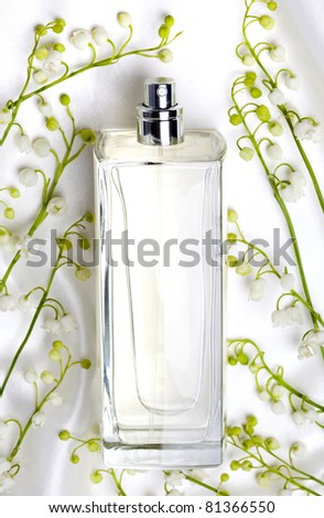 Lily of the valley and perfume bottle on white silk - stock photo