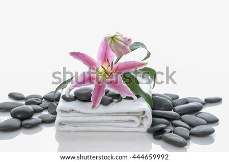 Lily on towel and pile of black stones  - stock photo