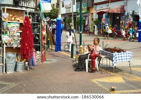 LIMA, PERU - FEBRUARY 13, 2012: Unidentified man selling kitchen utensils and wooden toys at the entrance of the market called Mercado No 1 de Surquillo on February 13, 2012 in Lima, Peru. - stock photo