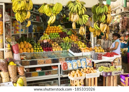 LIMA, PERU - FEBRUARY 13, 2012: Unidentified woman at fruit stand on the market called Mercado No 1 de Surquillo on February 13, 2012 in Lima, Peru. There are many fruit and vegetable markets in  Lima - stock photo
