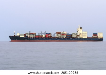 LIMASSOL, CYPRUS - 30 MAY 2014: A view of a Cargo ship carrying a large number of containers for freight, logistics in the port of Limassol city in Cyprus. - stock photo