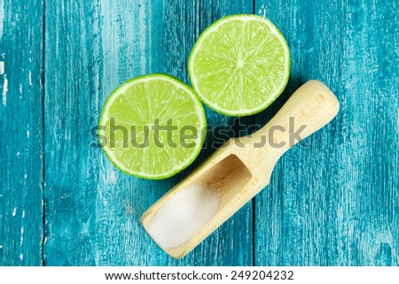 Lime and salt on blue wood background - stock photo
