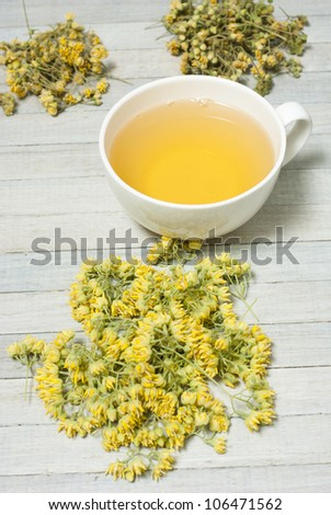 lime blossoms, herbal tea on white wooden