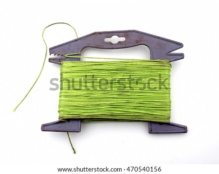 Lime color synthetic string on gray plastic handle close up white background.