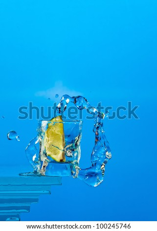 lime fall in a glass with tequila. - stock photo